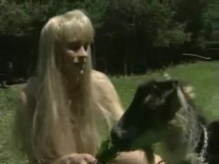 White-haired babe bares in field feeding goat with grass